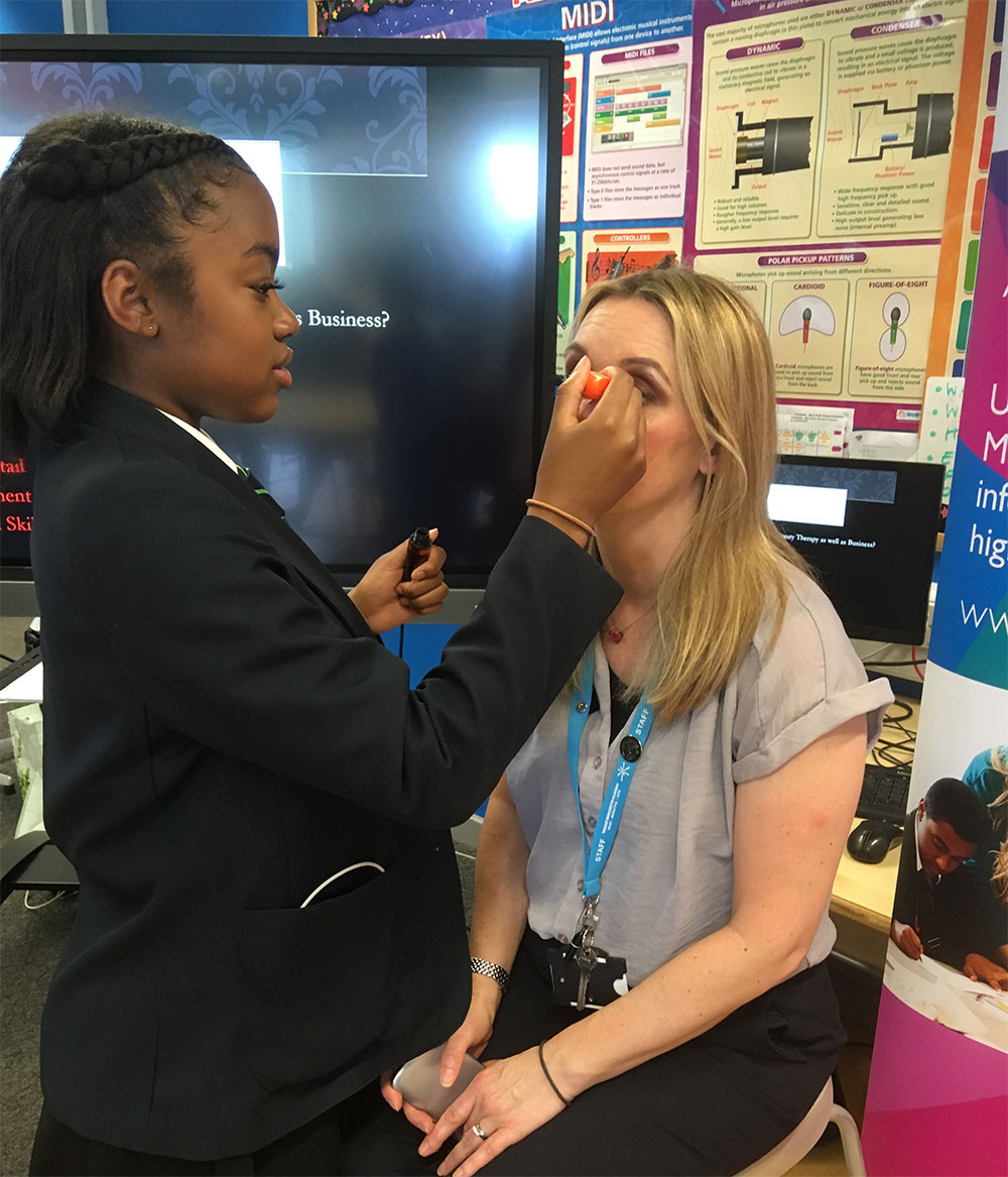 A student practices her make-up application technique at the